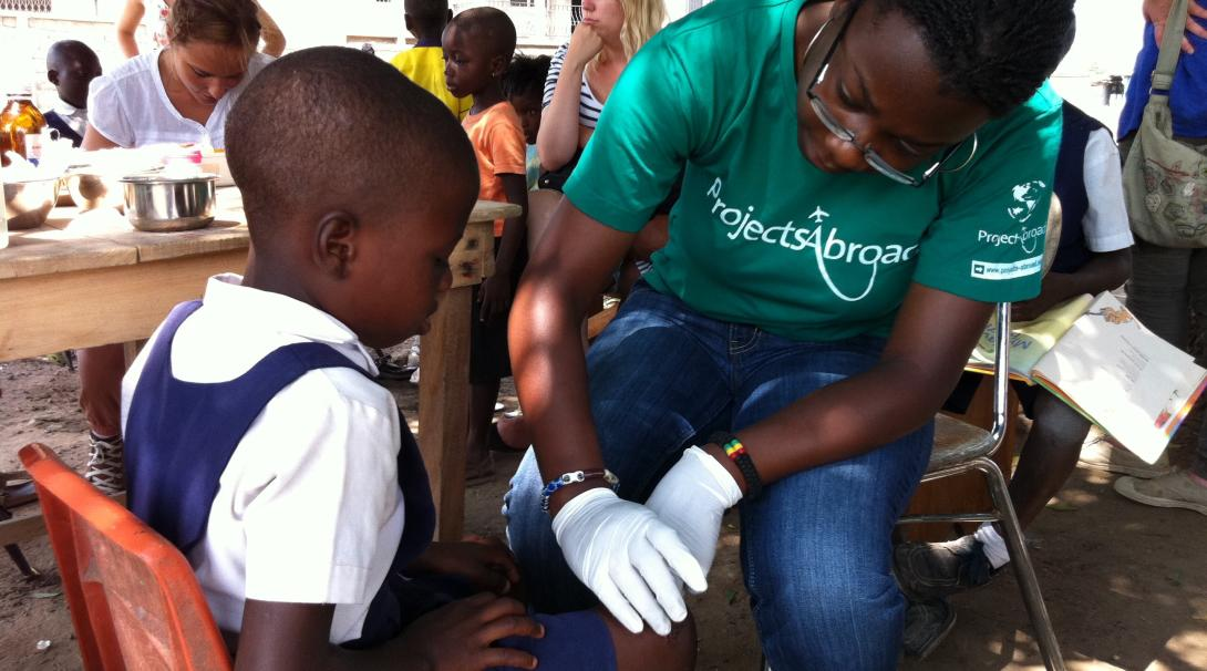 A Projects Abroad volunteer checks the leg of a young girl in Ghana as part of her physiotherapy internship.